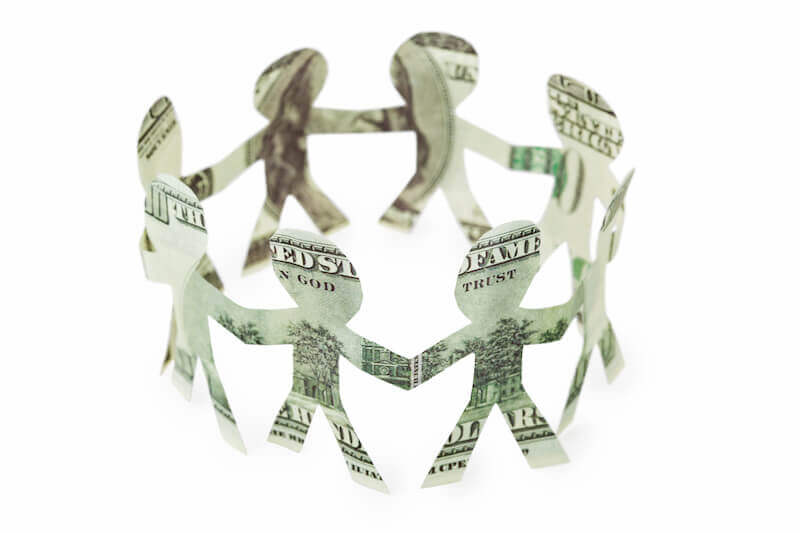 Dollar bills in the form of people holding hands, representing a cooperative financial institution