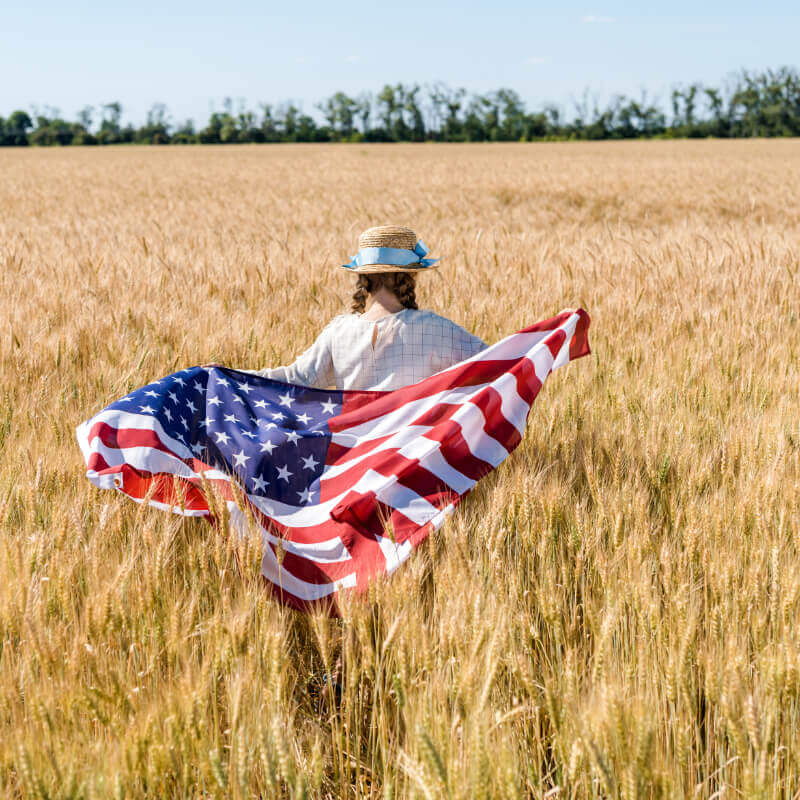 Child running through a field with the American flag, representing the time off on a holiday