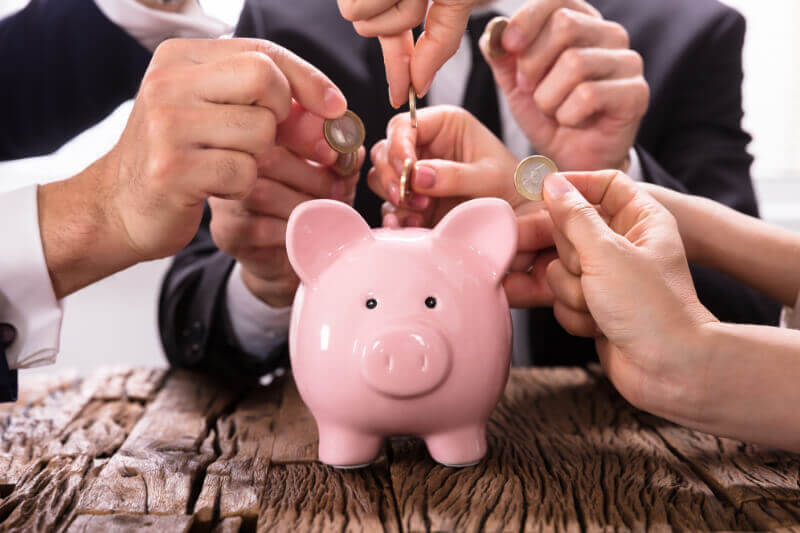 Multiple people putting coins in a piggy bank, representing a community pooling their savings to loan out to each other